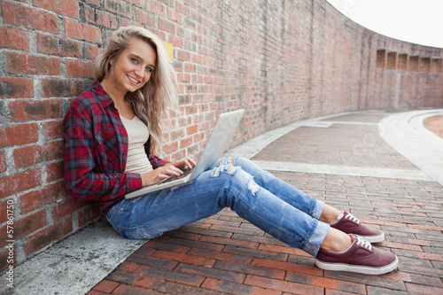 Cheerful gorgeous student leaning against wall using laptop