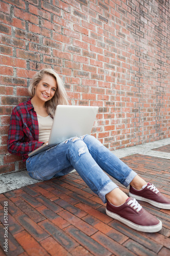 Happy gorgeous student leaning against wall using laptop