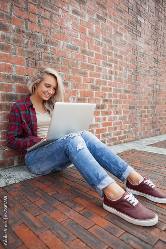 Lucky gorgeous student leaning against wall using laptop