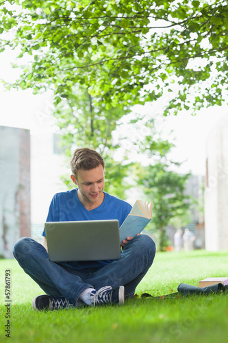 Focused handsome student sitting under tree studying