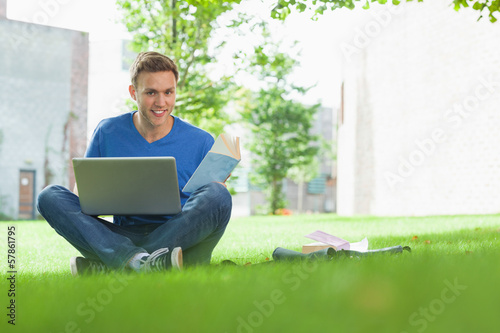 Smiling handsome student sitting under tree studying