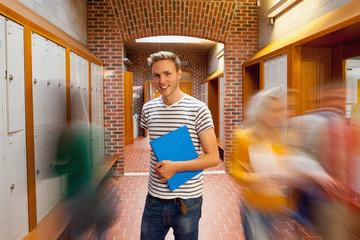 Smiling handsome student standing in hallway
