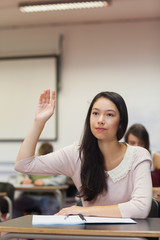 Focused asian student raising her hand in class