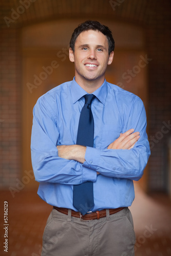 Cheerful handsome lecturer standing arms crossed
