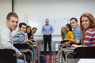 Students and lecturer smiling at camera in classroom