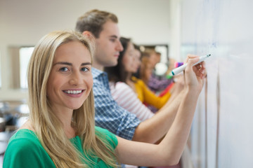 Students writing on the whiteboard together in class with one smiling at camera