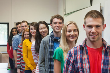 Students standing in a line in class smiling at camera