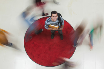 Happy student looking up at camera with others rushing around him