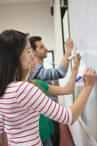 Students writing on the whiteboard together in class