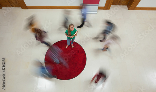 Blonde student looking up at camera with others rushing around