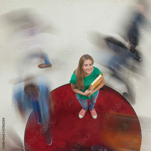 Blonde student looking up at camera with others rushing around her