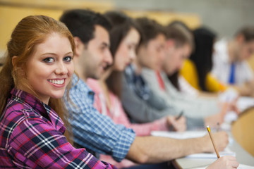 Row of students listening in a lecture hall with one smiling at camera