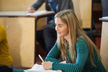 Smiling blonde student taking notes in a lecture hall