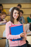 Happy brunette student standing in front of her class in lecture hall