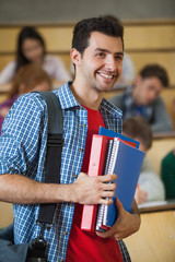 Happy student standing in front of his class in lecture hall
