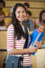 Happy student standing in front of her class in lecture hall smiling at camera