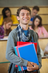 Smiling handsome student standing in front of his class in lecture hall