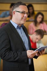 Lecturer holding tablet pc in front of class in lecture hall
