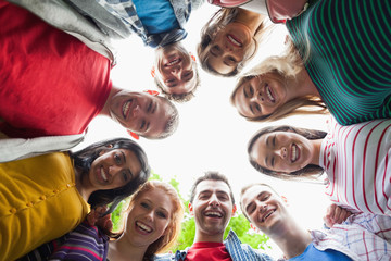 Group of students smiling down at camera in a circle on campus