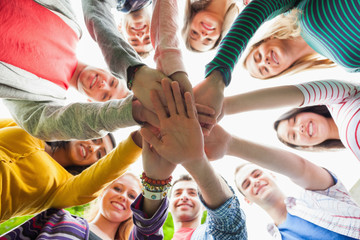 Group of smiling students putting hands in a circle on campus