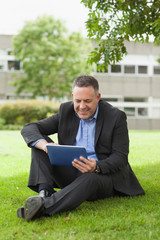 Happy lecturer using his tablet pc sitting outside on campus