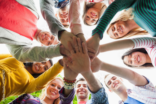 Group of happy students putting hands in a circle on campus