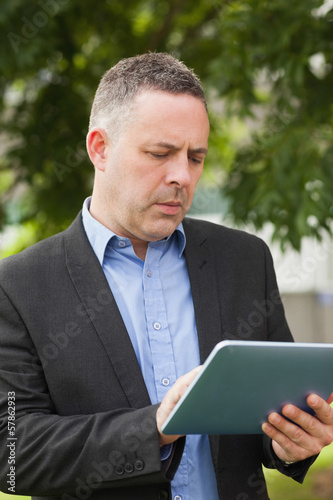Focused lecturer using his tablet outside on campus