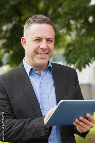 Smiling lecturer using his tablet outside on campus