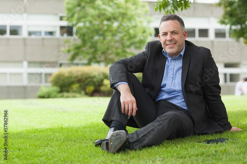 Cheerful lecturer sitting outside on campus looking at camera