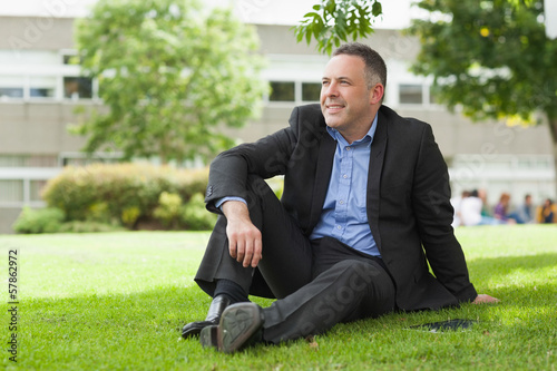 Happy lecturer sitting outside on campus looking away