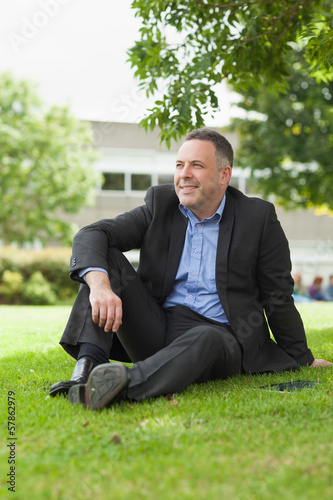Smiling lecturer sitting outside on campus looking away