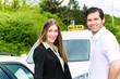 Taxifahrer und Kundin neben einem Taxi