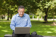 Cheerful lecturer sitting on bench using laptop on campus