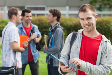 Happy male student using his tablet in front of his classmates outside