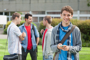 Cheerful male student sending a text in front of his classmates outside