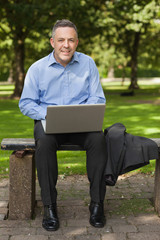 Smiling lecturer sitting on bench using laptop on campus