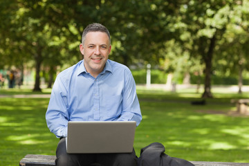 Cheerful professor sitting on bench using laptop on campus