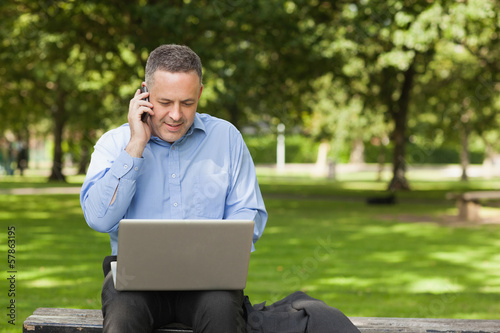 Cheerful professor talking on phone while sitting on bench using laptop on campus