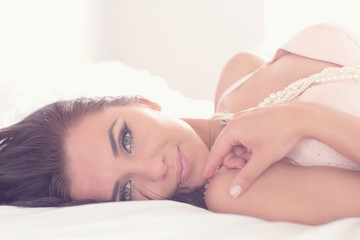 Cute woman wearing lingerie lying on her bed