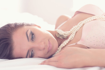 Thoughtful pretty woman wearing lingerie lying on her bed