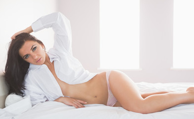 Sexy woman lying on her bed wearing a white shirt