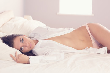 Beautiful slender woman wearing a white shirt lying on her bed