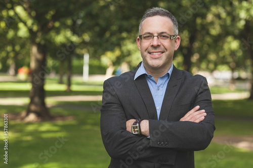 Happy professor looking at camera with arms folded on campus