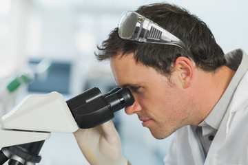 Handsome young scientist looking through a microscope
