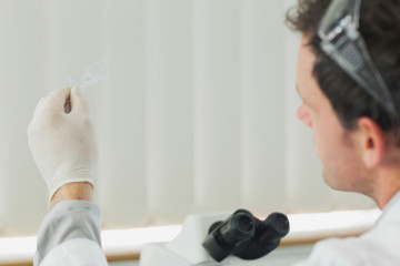 Attractive male scientist looking at microscope slide