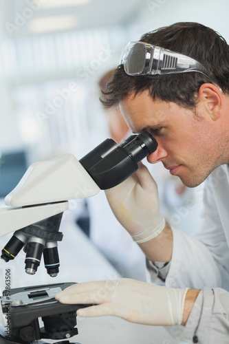 Attractive calm scientist looking through a microscope