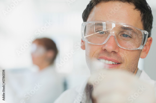 Handsome young scientist looking at microscope slide