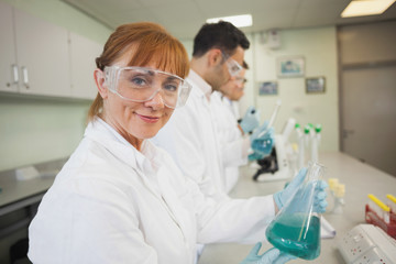 Content female scientist holding an erlenmeyer flask