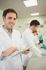Handsome young scientist using his tablet while standing in the laboratory