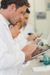Profile view of some scientists working with their white tablets